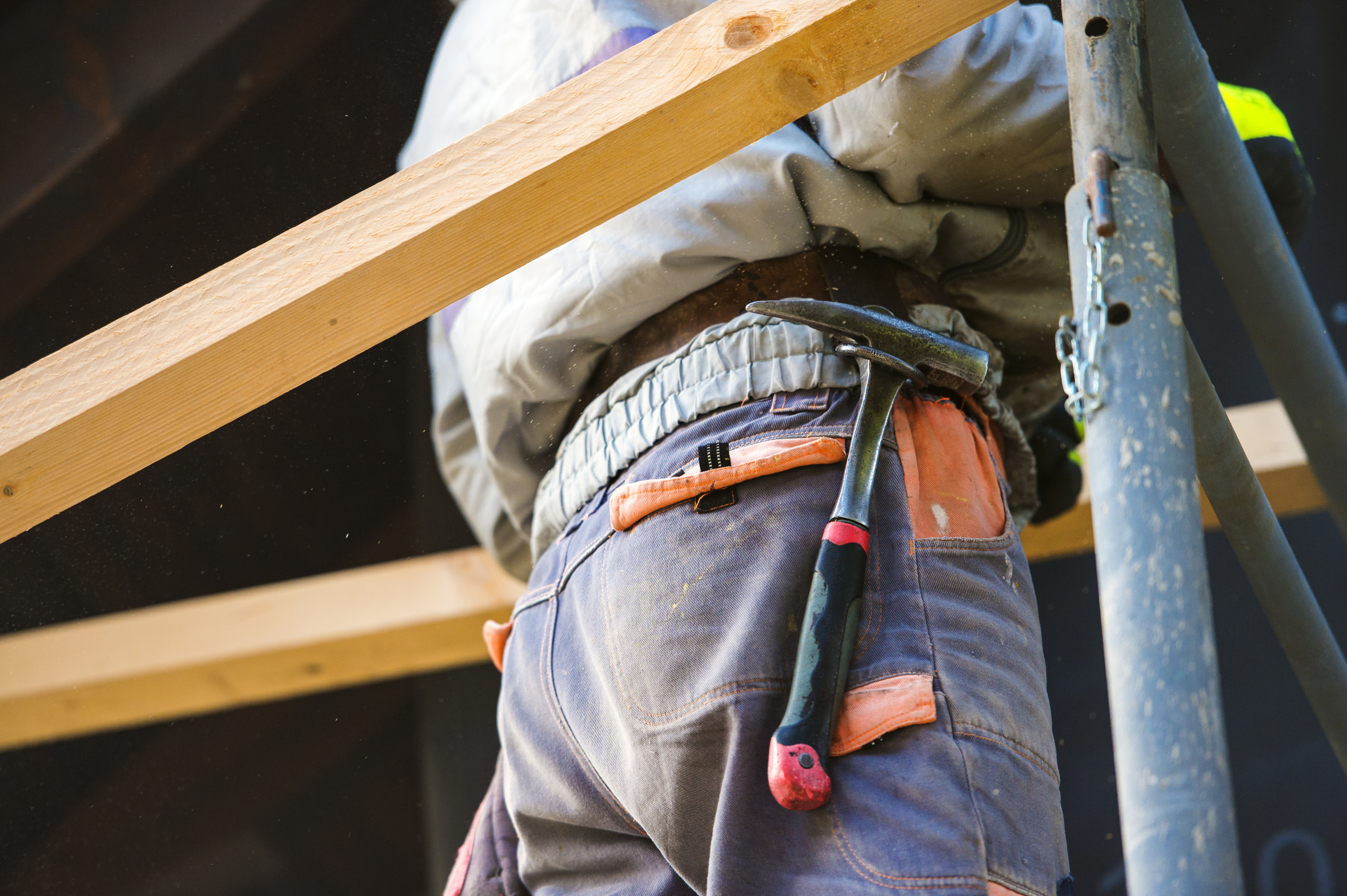 Construction worker in overalls with hammer standing on scaffold